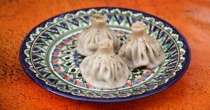 Georgian dish khinkali. On a ceramic plate royalty free stock photo