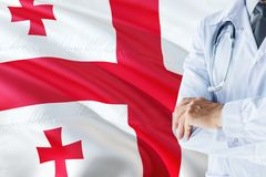 Georgian Doctor standing with stethoscope on Georgia flag background. National healthcare system concept, medical theme.  royalty free stock images