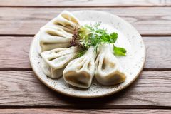 Georgian dumplings Khinkali with meat, greens on a wooden rustic table.  Stock Photo