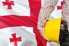 Georgian Engineer is holding yellow safety helmet with waving Georgia flag background. Construction and building concept.  stock photos