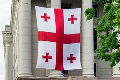 Georgian flag. Georgian flag hanging on the facade of old building with columns stock image