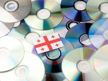 Georgian flag on top of CD and DVD pile isolated on white Stock Images