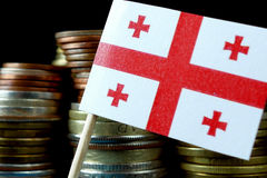 Georgian flag waving with stack of money coins Stock Image