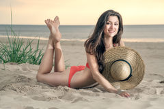 Georgian girl on the beach with a straw hat. A beautiful Georgian girl sunbathes on a beach in a straw hat royalty free stock images