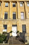 Georgian house. A large four storey Georgian terrace with sandstone columns on it's facade. The white door has a pair of topiary box plants on either side stock photos