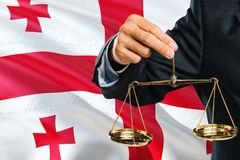 Georgian Judge is holding golden scales of justice with Georgia waving flag background. Equality theme and legal concept.  stock photo