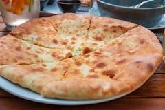 Georgian khachapuri imeruli. Georgian traditional food, hot khachapuri. Georgian khachapuri imeruli. Georgian traditional food, hot cut khachapuri stock image