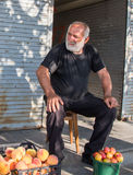 Georgian man selling fruits in a market. TELAVI, GEORGIA - CIRCA JULY 2016: a fruit salesman in a market stock photo