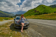 GEORGIAN MILITARY ROAD, GEORGIA - 29 JULY 2017: Young woman in f. Ront of Citroen car against Georgian Military Road Background Stock Photo