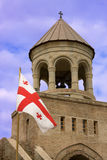 Georgian monastery. Georgian flag over orthodox monastery with blue sky Royalty Free Stock Image