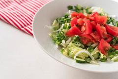Georgian salad tomatoes cucumbers, onions, on white table red napkin striped royalty free stock photography