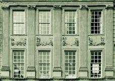 Georgian Sash Windows with old Ionic pillars and decoration. Horizontal black and white split toning photography Stock Photos