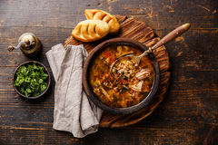 Georgian soup Kharcho with meat and rice. Traditional Georgian soup Kharcho with meat and rice on wooden background Royalty Free Stock Image