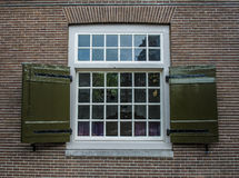 Georgian style window frame on brick house in Amsterdam. An old georgian sash style window on a brick house in Amsterdam with wooden shutters Stock Images