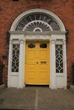 Georgian yellow door in the city Dublin in Ireland. Georgian yellow door in one of the streets in the city Dublin in Ireland in the summer Stock Image