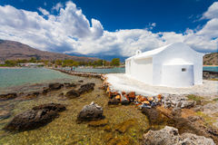 Georgioupolis , Island Crete, Greece - June 26, 2016: Saint Nicholas Church with the amazing white chapel is located in the sea o Royalty Free Stock Photo
