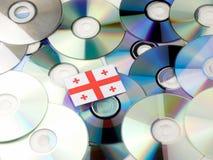 Georgische die vlag bovenop CD en DVD-stapel op wit wordt geïsoleerd Stock Afbeeldingen