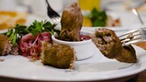 Georgische nationale keuken Het vlees wordt genomen met een vork en in saus ondergedompeld De kool en de koriander zijn in de pla stock video