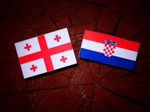 Georgisk flagga med den kroatiska flaggan på en isolerad trädstubbe Royaltyfria Bilder