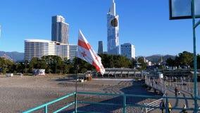 Georgisk flagga på invallningen av Batumi på bakgrunden av skyskrapor och stranden stock video