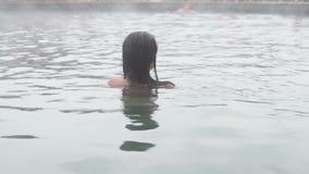 Geotermiska Spa Kvinna som kopplar av i pöl för varm vår Flicka som tycker om bada den opendoor handfatet med i varm mineralvatte arkivfilmer