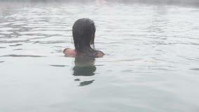 Geotermiska Spa Kvinna som kopplar av i pöl för varm vår Flicka som tycker om bada den opendoor handfatet med i varm mineralvatte stock video