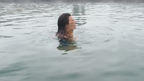 Geotermiska Spa Kvinna som kopplar av i pöl för varm vår Flicka som tycker om bada den opendoor handfatet med i varm mineralvatte lager videofilmer