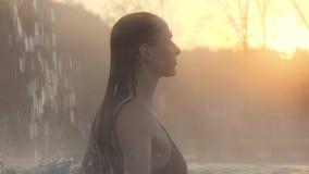 Geotermiska Spa Kvinna som utomhus kopplar av i pöl för varm vår arkivfilmer