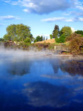 Geothermal Activity of Kuirau Park, New Zealand. Geothermal Activity of Kuirau Park, with wooden lookout and cloud reflections through the steam. Rotorua, New Royalty Free Stock Photo