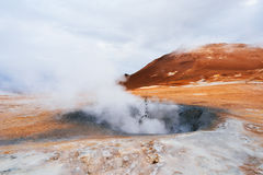Geothermal area Namafjall with steam eruptions, Iceland, Europe. Landscape with eruption steam. Geothermal area Namafjall, Iceland, Europe. Overcast day Stock Photos