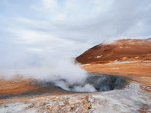 Geothermal area Namafjall with steam eruptions, Iceland, Europe. Landscape with eruption steam. Geothermal area Namafjall, Iceland, Europe. Overcast day Royalty Free Stock Photography
