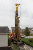 Geothermal Drilling. Geothermal heat system in the neighborhood in a tight spot stock photo