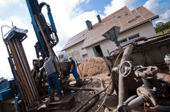 Geothermal drilling for house. Two workmen using geothermal drilling machinery outside modern house or home Royalty Free Stock Photos