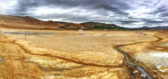Geothermal mineral deposits. A boardwalk leads through mineral deposits smoking against the Icelandic terrain stock image
