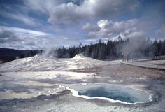 Geothermal Pool Yellowstone. Steaming geothermal pool in Old Faithful Geyser Park erupting from a landscape that looks more like the surface of the moon than a Royalty Free Stock Photo