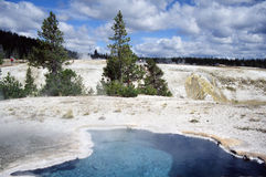 Geothermal Pool in Yellowstone Park. Serene landscape featuring brilliantly blue geothermal pool nested in starkly white, crusted surface of Geyser Park. Blue Stock Images
