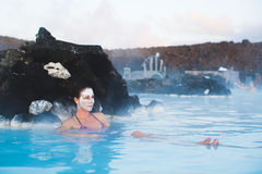 Geothermal spa. Woman relaxing in geothermal spa in hot spring pool in Iceland. Girl enjoying bathing in a blue water lagoon with famous healing mud on her face Royalty Free Stock Photo