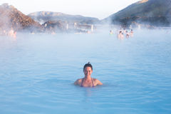 Geothermal spa. Woman relaxing in geothermal spa in hot spring pool in Iceland. Girl enjoying bathing in a blue water lagoon with famous healing mud stock photo