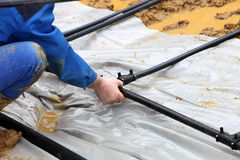 Geothermische Rohre der Handwerker gelegt in den Boden Stockbild