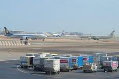 Gepäck karrt im Hintergrund den Flugplatz des internationalen Flughafens von Abu Dhabi Lizenzfreies Stockbild