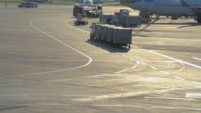 Gepäcktraktor trägt Behälter auf dem Gebiet des Flughafens Vnukovo stock video footage