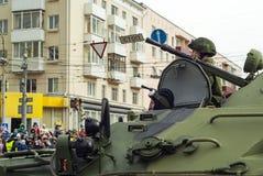 Gepantserde personeelsdrager met een bemanning op een stadsstraat na de Victory Day-parade stock afbeelding