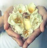 Geparfumeerd nam olie in de palmen toe Bloemengeuren in een minifles stock foto's