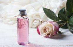 Geparfumeerd rozewater in een fles op een houten lijst stock fotografie