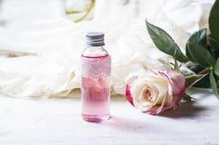 Geparfumeerd rozewater in een fles op een houten lijst royalty-vrije stock afbeeldingen