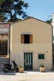 Geparkeerde autoped dichtbij de deur van het plattelandshuisje in het dorp in Kroatië stock foto's