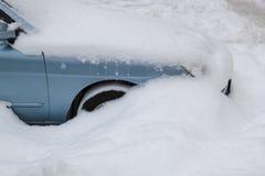 Geparkeerde blauwe auto onder sneeuwdekking De achtergrond van het de winterparkeren royalty-vrije stock fotografie