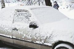 Geparkeerde die auto met sneeuw wordt behandeld - sneeuwonweer, auto na een zware sneeuwval, heel wat sneeuw op de auto, auto in  Stock Foto