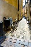 Geparkeerde fiets in smalle straat, Stockholm Stock Foto's