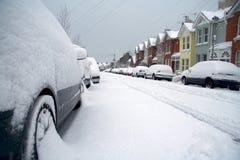 Geparkte Autos auf schneebedeckter Wohnstraße stockfoto